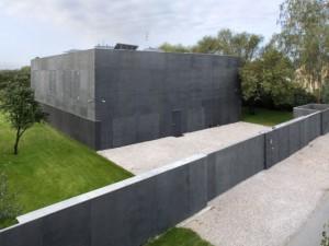 Часть коттеджа выходящая на дорогу выглядит как неприступная бетонная крепость