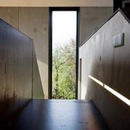 Узкое высокое окно коттеджа напротив лестницы