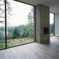 Через большие окна коттеджа открывается прекрасный вид на лес и озеро