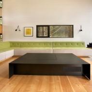 Гостиная с большим низким столом черного цвета и белыми стенам