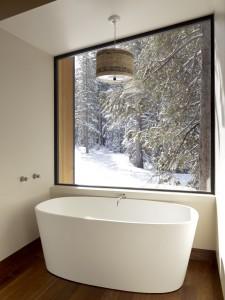 Высокая отдельно стоящая ванна в ванной комнате коттеджа
