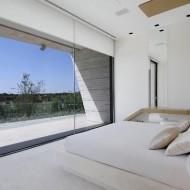 Светлый интерьер спальни в коттедже; высокие потолки