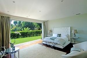 Спальня с окном во всю стену; дизайн интерьеров в коттедже