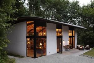 Современный коттедж с полукруглой крышей и высокими окнами